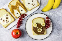 Funny animal sandwich for kids shaped cute bear, panda, fox, rabbit. With peanut butter, honey, chocolate paste and banana. Top vew stock photo