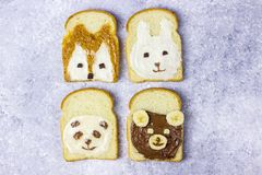Funny animal sandwich for kids shaped cute bear, panda, fox, rabbit. With peanut butter, honey, chocolate paste and banana. Top vew royalty free stock photo