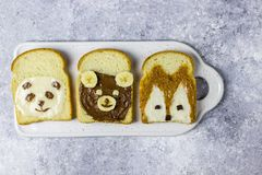Funny animal sandwich for kids shaped cute bear, panda, fox, rabbit. With peanut butter, honey, chocolate paste and banana. Top vew royalty free stock image