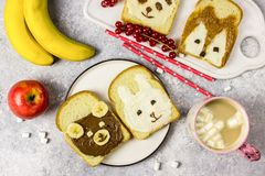 Funny animal sandwich for kids shaped cute bear, panda, fox, rabbit. With peanut butter, honey, chocolate paste and banana. Top vew stock image