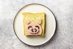 Funny animal sandwich for kids shaped cute pig with boiled sausage and olives. On white plate on grey background, food art idea. Top view stock images
