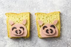 Funny animal sandwich for kids shaped cute pig with boiled sausage and olives. On white plate on grey background, food art idea. Top view royalty free stock images