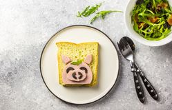 Funny animal sandwich for kids shaped cute pig with boiled sausage and olives. On white plate on grey background, food art idea. Top view stock photo