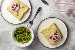 Funny animal sandwich for kids shaped cute pig with boiled sausage and olives. On white plate on grey background, food art idea. Top view stock photos