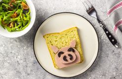 Funny animal sandwich for kids shaped cute pig with boiled sausage and olives. On white plate on grey background, food art idea. Top view stock photography
