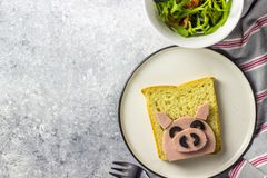 Funny animal sandwich for kids shaped cute pig with boiled sausage and olives. On white plate on grey background, food art idea. Top view royalty free stock photography