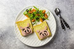 Funny animal sandwich for kids shaped cute pig with boiled sausage and olives. On white plate on grey background, food art idea. Top view royalty free stock photo