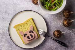 Funny animal sandwich for kids shaped cute pig with boiled sausage and olives. On white plate on grey background, Pig shaped sandwiches for new year 2019 stock photo