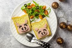 Funny animal sandwich for kids shaped cute pig with boiled sausage and olives. On white plate on grey background, Pig shaped sandwiches for new year 2019 royalty free stock photo