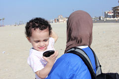 Funny arab muslim egyptian baby girl with her mother Stock Photos
