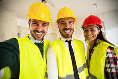 Funny architects workers taking selfie at contruction site. Teamwork Stock Images