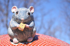 Funny artificial mouse with cheese sitting on the roof Stock Image