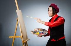 Funny artist in dark studio Stock Images