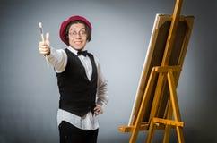 The funny artist in dark studio Stock Photo