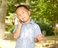 Funny asian boy with a mobile phone in a park Royalty Free Stock Images