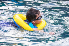 Funny asian boy with swim tube in pool. Outdoor. Stock Photography