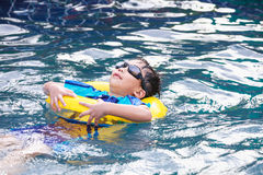 Funny asian boy with swim tube in pool. Outdoor. Royalty Free Stock Photography
