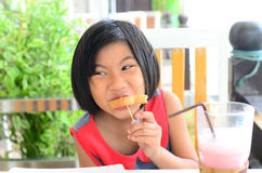 Funny Asian girl eating tasty bread Stock Images
