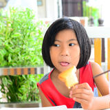 Funny Asian girl eating tasty bread Royalty Free Stock Images