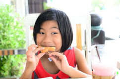 Funny Asian girl eating tasty bread Stock Photography