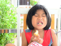 Funny Asian girl eating tasty bread Stock Photos