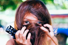 Funny Asian girl hiding her face from her hair Stock Images