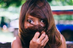 Funny Asian girl hiding her face from her hair Stock Photos