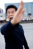 Funny Asian Karate Man. An angry asian man performing karate moves toward the camera Royalty Free Stock Photography
