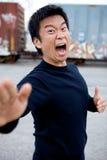 Funny Asian Karate Man. An angry asian man performing karate moves toward the camera Royalty Free Stock Image