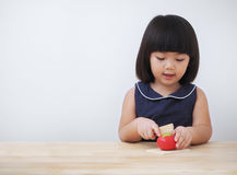 Funny asian kid girl playing with wooden cooking toy, Little chef preparing food on kitchen counter Royalty Free Stock Image