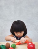 Funny asian kid girl playing with wooden cooking toy, Little chef preparing food on kitchen counter Royalty Free Stock Photography