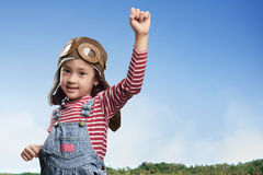 Funny asian little girl in aviator hat and goggles playing at fi Royalty Free Stock Photography