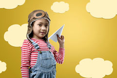 Funny asian little girl in aviator helmet playing airplane toy Royalty Free Stock Photography