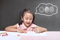 Funny asian little girl with crayon drawing easter egg. On the table Royalty Free Stock Photography