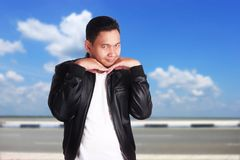 Funny Asian Man Act Feminine. Portrait of funny young Asian man doing flirtatious feminine act, hands under chin, over cloudy blue sky background Royalty Free Stock Photos