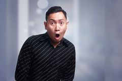 Funny Young Asian Man Amazed Shocked Gesture. Funny Asian man amazed shocked or surprised expression with mouth open Royalty Free Stock Image