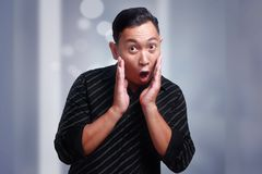 Funny Young Asian Man Amazed Shocked Gesture. Funny Asian man amazed shocked or surprised expression with mouth open, touching cheek Royalty Free Stock Photo
