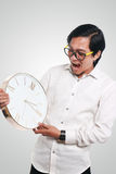 Funny Asian Man With a Clock Royalty Free Stock Image