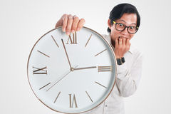 Funny Asian Man With a Clock Royalty Free Stock Photography