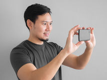 Funny Asian man taking photo with smartphone. Royalty Free Stock Image