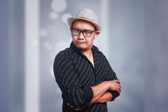 Cynical Asian Man Expression. Funny Asian man wearing eyeglasses and panama hat shows cynical unhappy angry facial expression with arms crossed Royalty Free Stock Image