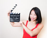 Funny asian woman red dress with movie clapperboard on white Stock Image