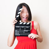 Funny asian woman red dress with movie clapperboard on white Royalty Free Stock Photos
