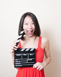Funny asian woman red dress with movie clapperboard on white Royalty Free Stock Photo