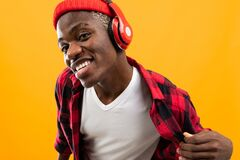 Free Funny Attractive American Black Man Stylishly Dressed Listens To Music On Headphones On A Yellow Studio Background Stock Photo - 171544530