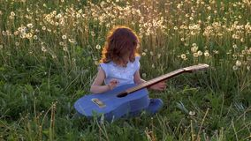 Funny attractive little girl sits in the grass and plays the jeans guitar. field with dandelions in spring bloom at sunset. concep. T of children development and