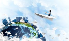 Funny aviator sitting in paper plane. And holding steering wheel. Pilot driving paper plane in cloudy blue sky. Spherical view of modern city with high royalty free illustration