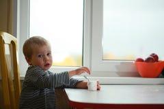 Funny babe blondes licks  finger with yogurt. Funny babe boy blondes licks  finger with yogurt Stock Image