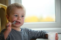 Funny babe blondes licks  finger with yogurt. Funny babe boy blondes licks  finger with yogurt Royalty Free Stock Photography
