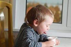 Funny babe blondes licks  finger with yogurt. Funny babe boy blondes licks  finger with yogurt Stock Images